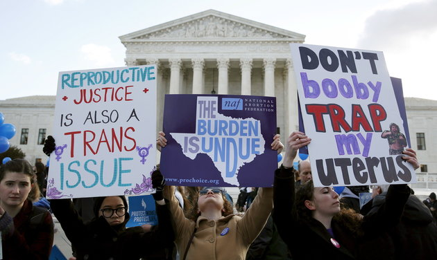 Protesters hold signs in front of the U.S. Supreme Court in Washington